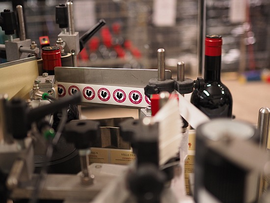 Wein etikettieren und verpacken, eine Etikettiermaschine übernimmt einen Teil davon