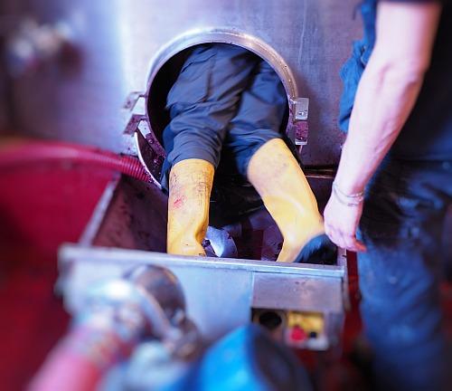 ulkige Arbeiten im Weingut, Traubenschalen Edelstahltank herausschaffen